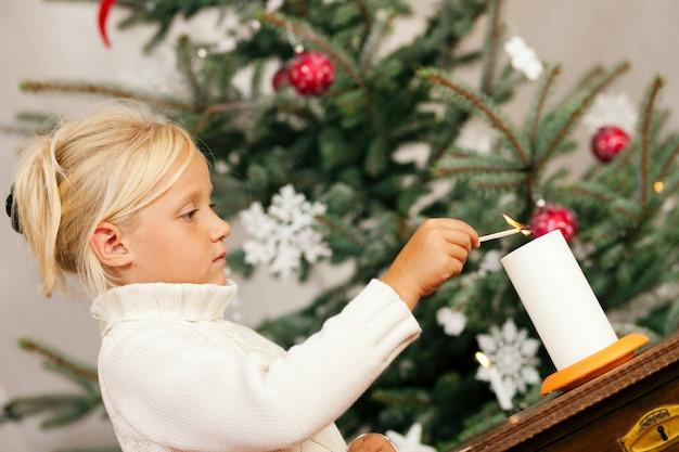 Kind, das weihnachtskerzen beleuchtet