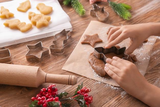 Kind, das weihnachtsplätzchen am tisch vorbereitet