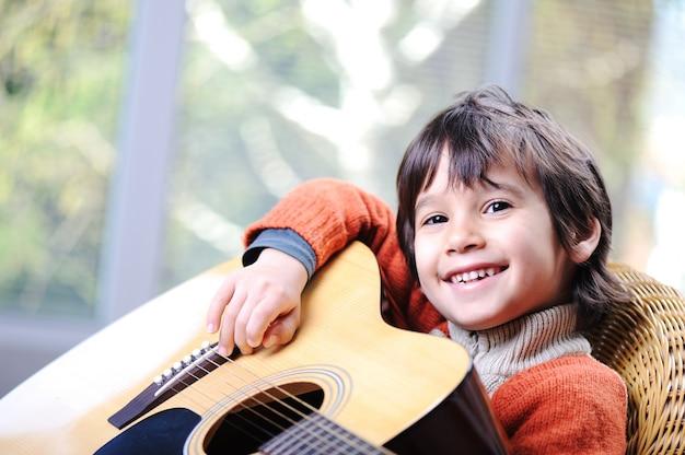 Kind, das zu hause gitarre spielt