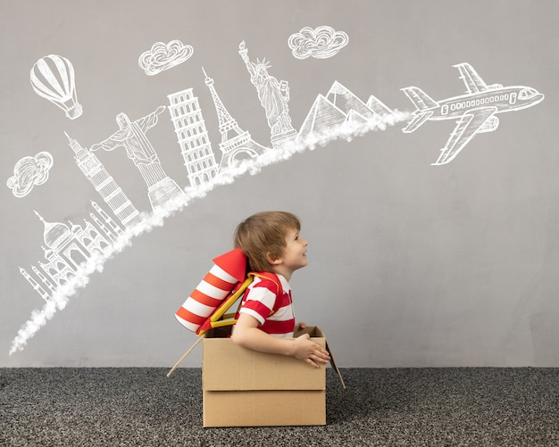 Kind, das zu hause spielt. kind sitzt im karton. kind träumt von reisen. kinderphantasie und reisekonzept