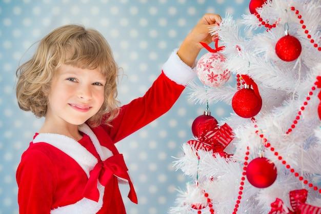 Kind, das zu hause spielt. weihnachtsbaum. weihnachtsferienkonzept