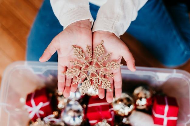 Kind, das zu hause weihnachtsbaum verziert. hält eine goldene schneeflocke