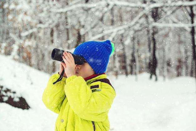 Kind, das zum monokular schaut. winterurlaub mit der familie. winterspaß in der natur. netter kinderforscher im verschneiten wald.