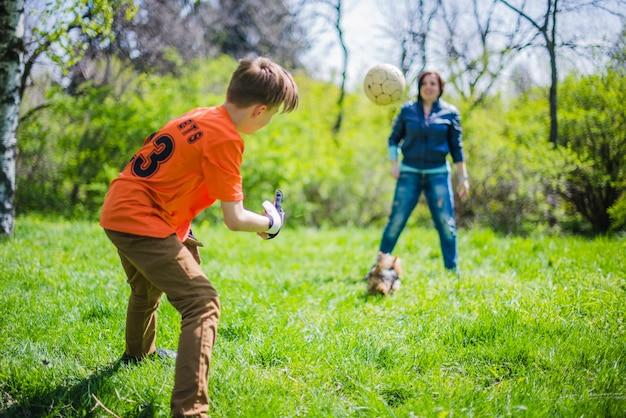 Kind, der den ball zu seiner mutter wirft