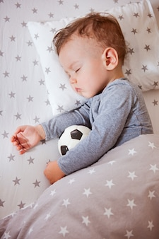 Kind, der junge schläft in einem babybett, das einen fußball umarmt
