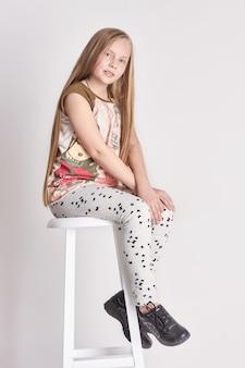 Kind des jungen mädchens mit dem langen haar, das auf einem stuhl sitzt. lächeln freude gefühle auf ihrem gesicht