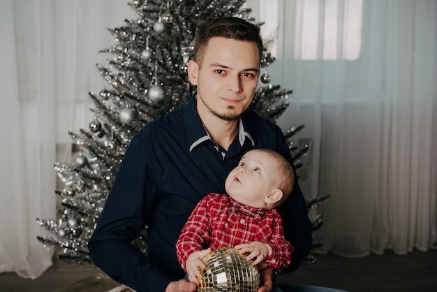 Kind des kleinen jungen in den armen seines vaters des weihnachtsbaums