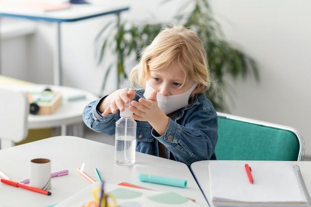 Kind desinfiziert hände im klassenzimmer