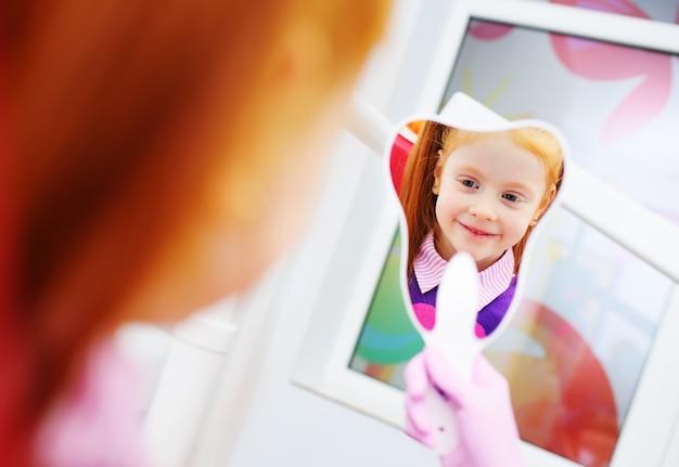Kind-ein kleines rothaariges mädchen, das das schauen im spiegel sitzt im zahnmedizinischen stuhl lächelt.