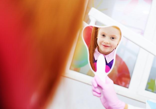 Kind-ein kleines rothaariges mädchen, das im spiegel schauend lächelt, der im zahnmedizinischen stuhl sitzt.