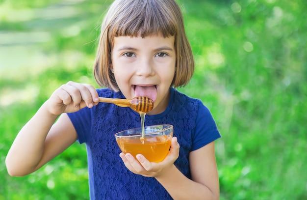 Kind einen teller mit honig in den händen