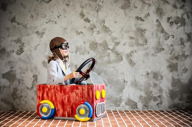 Kind fährt ein auto aus karton. kind hat spaß zu hause. reise- und urlaubskonzept