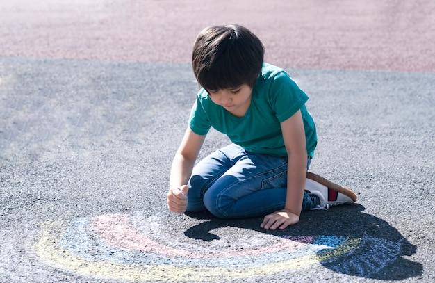 Kind färbt regenbogen auf pflaster, kind, das regenbogen mit bunten kreiden auf fußweg während covid-19-quarantäne zu hause zeichnet