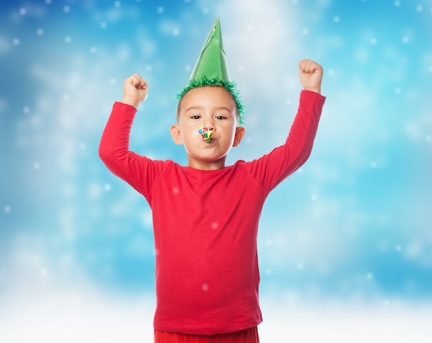 Kind feiert mit erhobenen armen und partygebläse
