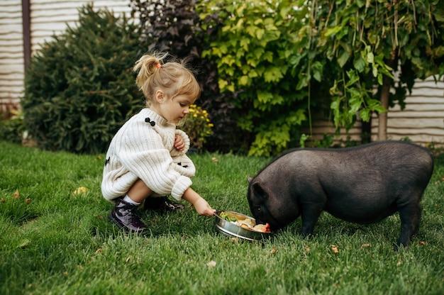 Kind füttert schwarzes schwein im garten und kümmert sich um tiere. kind mit schweinchen posiert auf hinterhof. glückliche kindheit
