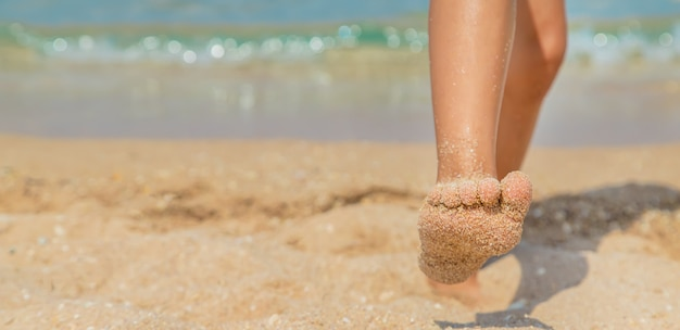Kind geht am strand entlang und hinterlässt spuren im sand