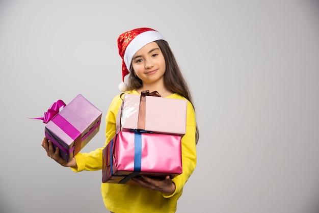 Kind gekleidet in den roten hut des weihnachtsmannes, der viele weihnachtsgeschenke trägt. hochwertiges foto