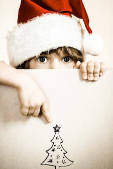 Kind gekleidet in santa claus mit papierleerzeichen. weihnachtsferienkonzept