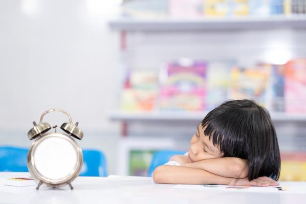 Kind gelangweilt lernen, auf dem tisch zu schlafen
