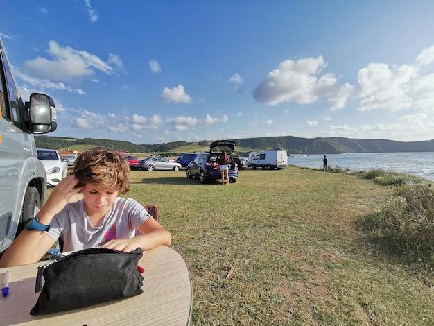 Kind genießt die ferien malen mitten in der natur auf einem campingplatz im wohnmobil