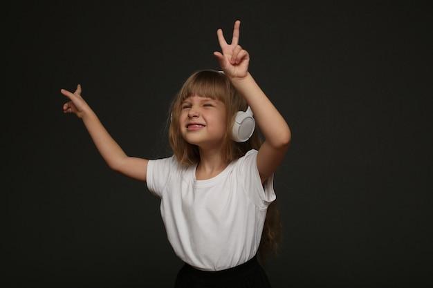 Kind genießt musik in ihren großen weißen kopfhörern und lächelt. blaue augen blondes haarmädchen stehend und musik hören. hochwertiges foto