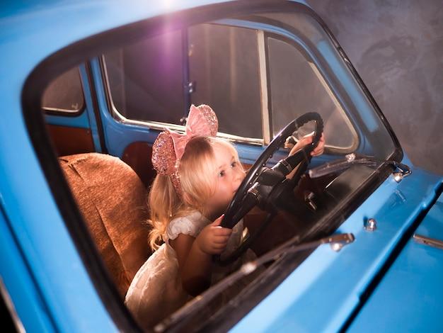 Kind gibt vor, auto zu fahren, das auf vorderem fahrersitz mit den händen auf lenkung sitzt.