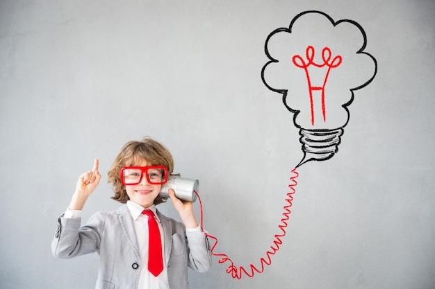 Kind gibt vor, geschäftsmann zu sein. kind, das zu hause spielt. fantasie, idee und start-up-konzept. zurück zur schule