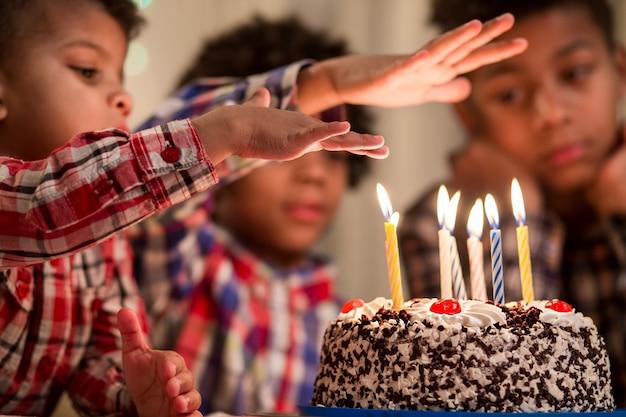 Kind hält die hand über die kerze jungen übergibt kuchen kerzenfreunde werden beeindruckt sein, ich werde dir einen trick zeigen
