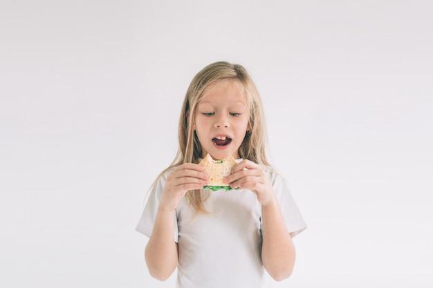 Kind hält ein stück hamburger