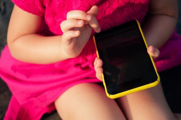 Kind hält ein verschlossenes telefon in der hand