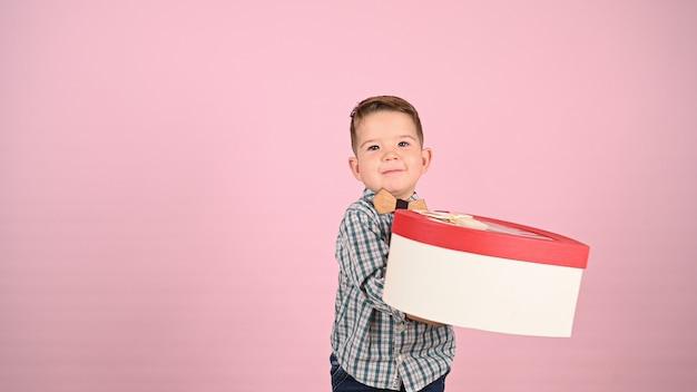 Kind hält eine geschenkbox, herzförmig. hochwertiges foto