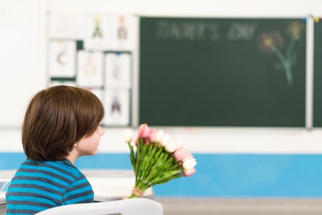 Kind hält einen blumenstrauß für seinen lehrer