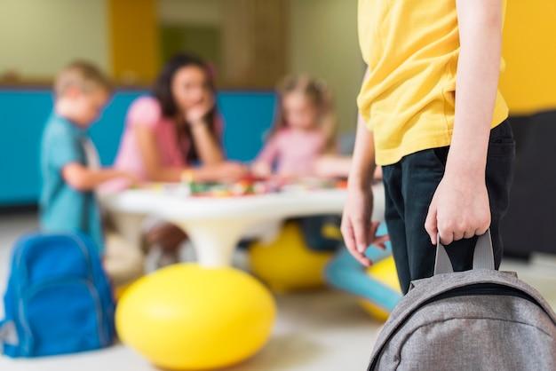 Kind hält einen rucksack mit kopierraum