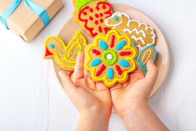 Kind hält einen selbst gemachten gemalten lebkuchen (plätzchen) auf weißem hölzernem hintergrund unter tannenzweigen und geschenken. süßes geschenkkonzept des weihnachten und des neuen jahres. lustige süße lebensmittelnahaufnahme. kopieren sie platz für text