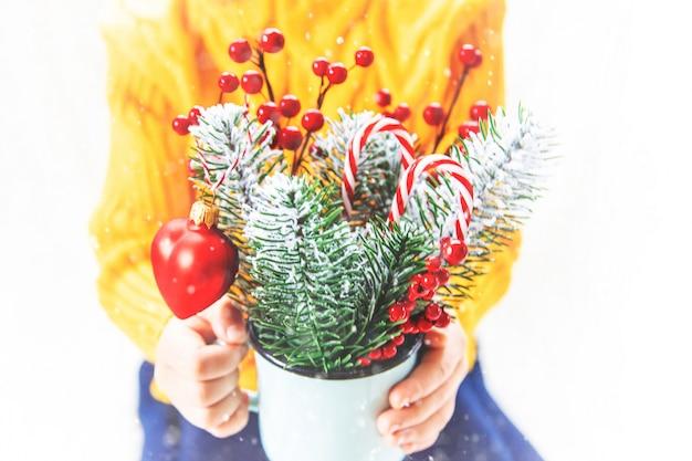 Kind hält einen weihnachtsdekor und geschenke auf einem weißen hintergrund. selektiver fokus