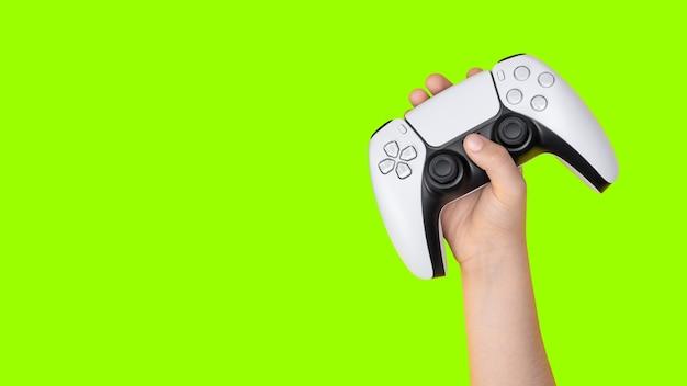 Kind hält gamecontroller mit grünem hintergrund zum zuschneiden