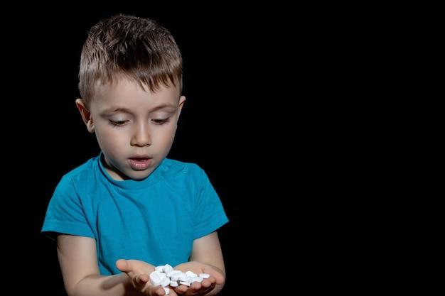 Kind hält haufen von weißen pillen und drogen in seiner handfläche auf schwarzem hintergrund. konzept der drogenabhängigkeit und selbstmord.