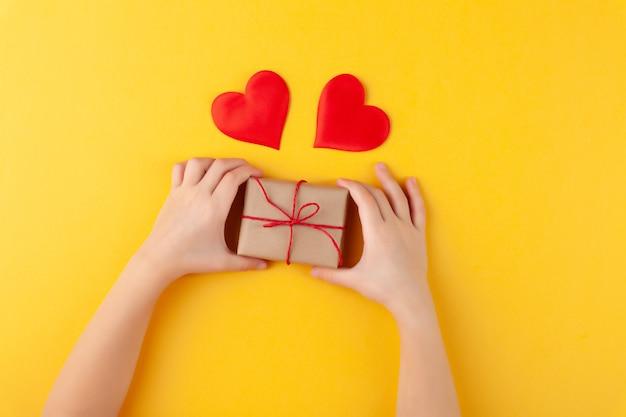 Kind hält in händen überraschungsgeschenkbox, viele rote herzen, liebe und valentinstag konzept