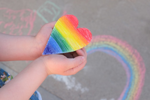 Kind hält in seinen handflächen ein papierherz, das in regenbogenfarben des regenbogens der lgbt-gemeinschaft gemalt ist, kreide auf dem bürgersteig, monatsstolz-konzept - temporäre kunst