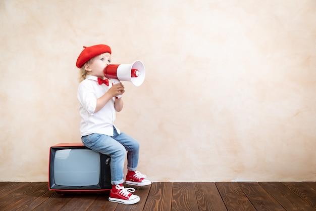 Kind hält lautsprecher. kind, das durch vintage-megaphon schreit. wirtschaftsnachrichten-konzept