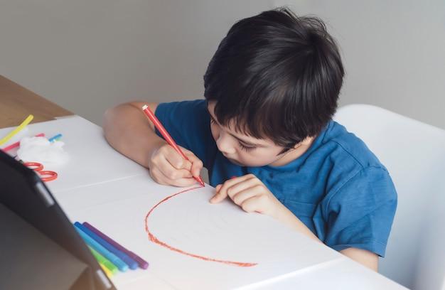 Kind hält roten stift, der regenbogen auf papier färbt Premium Fotos