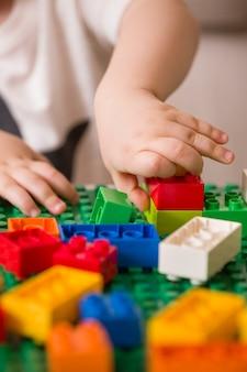 Kind hat spaß beim spielen mit bunten plastiksteinen und leuchtenden würfeln am tisch