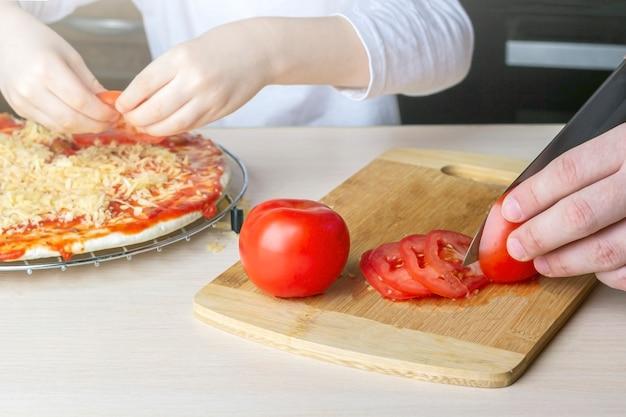 Kind helfen seinem vater, hausgemachte pizza zu kochen. familienzeitvertreib während der quarantäne. prozess des kochens von pizza durch kind. bleib zu hause, soziale distanz und selbstisolation.