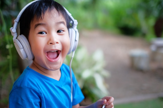 Kind hören musik mit kopfhörer zu hause. schaue aufgeregt gesichtsausdruck.