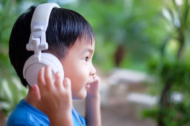 Kind hören musik mit kopfhörer zu hause. seitengesicht, das mit kopienraum schaut.