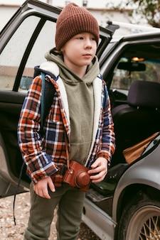 Kind im freien mit auto auf einem roadtrip