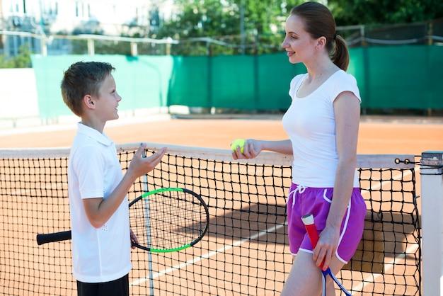Kind im gespräch mit frau auf dem tennisplatz