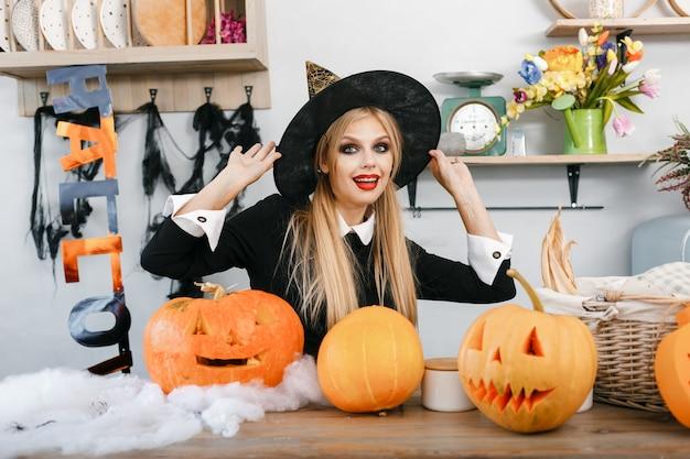 Kind im gruseligen hexenkostüm. halloween-party und dekorationskonzept. kleine hexe mit schwarzem hut. . hochwertiges foto