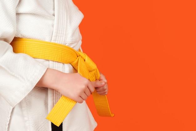 Kind im karate-kimono, das seinen gelben gürtel hält, nahaufnahme junge, der karate auf farbigem hintergrund praktiziert