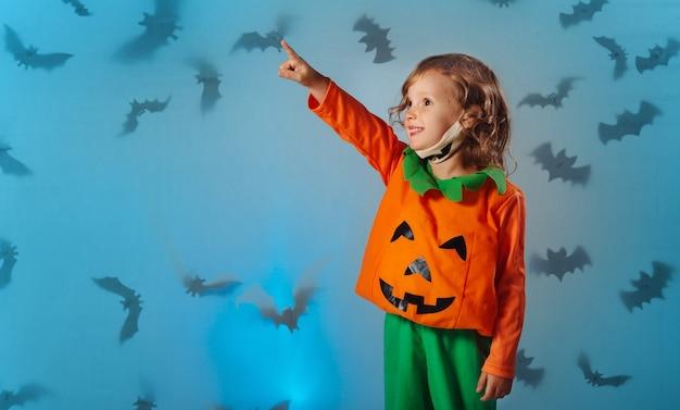 Kind im kürbiskarnevalskostüm und medizinischer maske zeigt mit der hand auf fledermäuse an halloween
